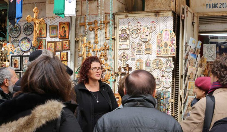 a tour taking place in the city of Jerusalem next to a tourist shop