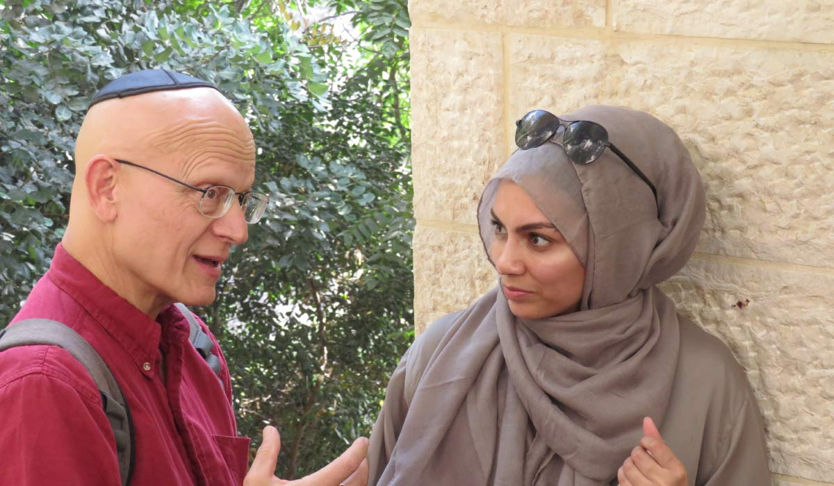 A Jewish man and Muslim woman talking to each other