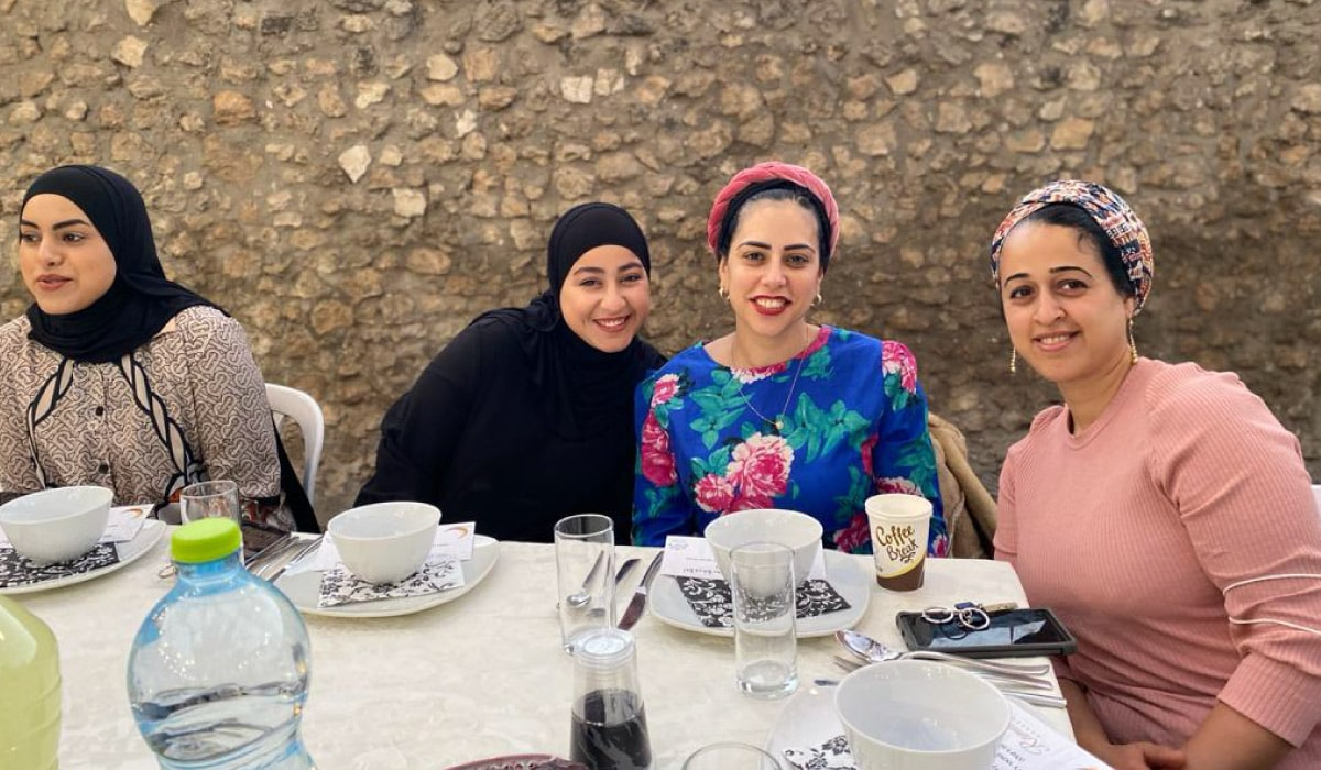 4 women smiling together at iftar dinner