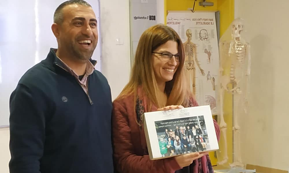 two teachers showing a picture and smiling