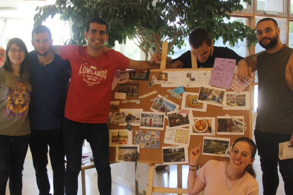 A group of university students showcasing their work on a board